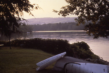 Hazy lake scene with trees and boats in foreground